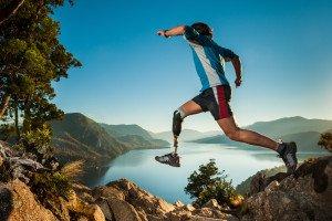 Hombre lisiado saltando en la montaña